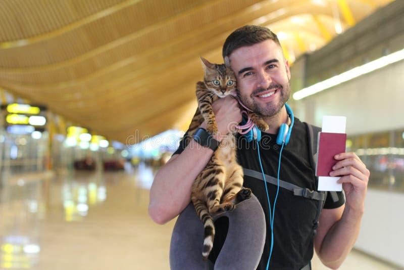 Uomo bello che viaggia con il suo gatto fotografia stock