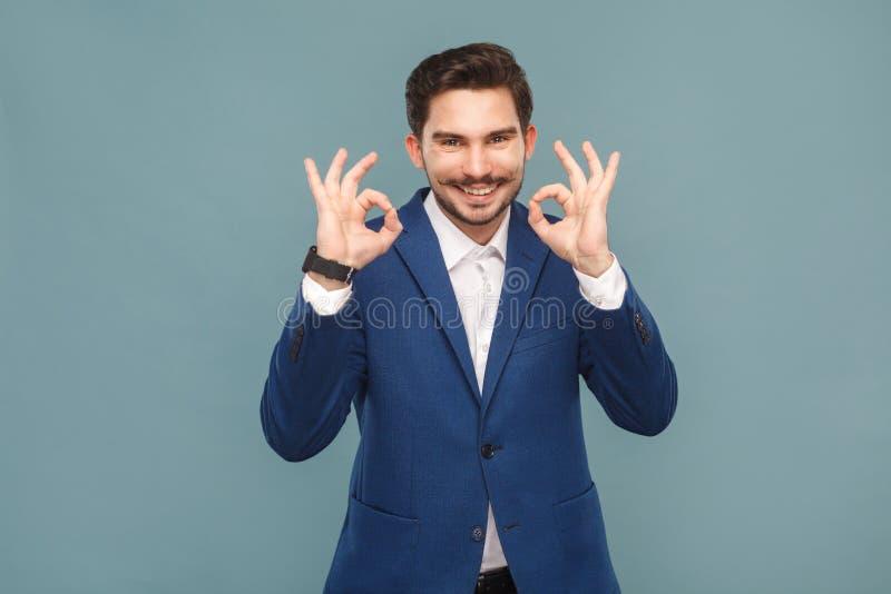 Uomo bello con i baffi che mostrano segno giusto alla macchina fotografica fotografia stock