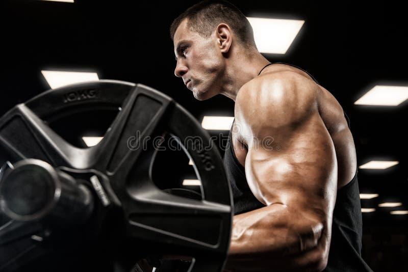 Uomo bello con i grandi muscoli, posanti alla macchina fotografica nella palestra fotografia stock libera da diritti