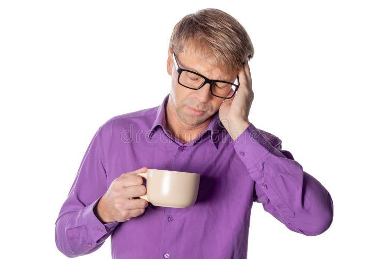 Uomo bello con i vetri sopra fondo bianco che beve una tazza di caffè sollecitata con la mano sulla testa Emicrania, freddo ed in immagine stock libera da diritti