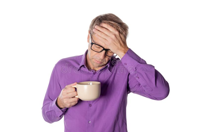 Uomo bello con i vetri sopra fondo bianco che beve una tazza di caffè sollecitata con la mano sulla testa Emicrania, freddo ed in fotografie stock