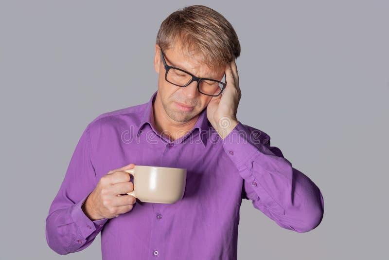 Uomo bello con i vetri sopra fondo grigio che beve una tazza di caffè sollecitata con la mano sulla testa Emicrania, freddo ed in immagini stock libere da diritti
