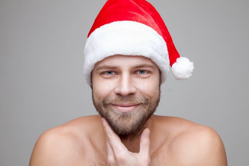 Uomo bello con la barba che porta un cappello di Natale fotografia stock libera da diritti