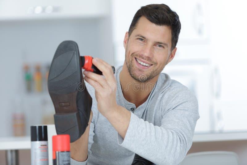 Uomo bello con la scarpa di cuoio del nero di pulizia di spazzola immagini stock