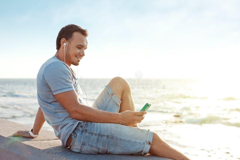 Uomo bello con lo smartphone mobile che si siede vicino all'oceano fotografia stock