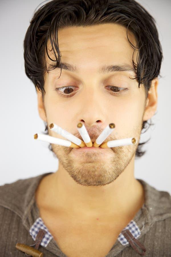 Uomo bello con molte sigarette nella sua bocca immagine stock