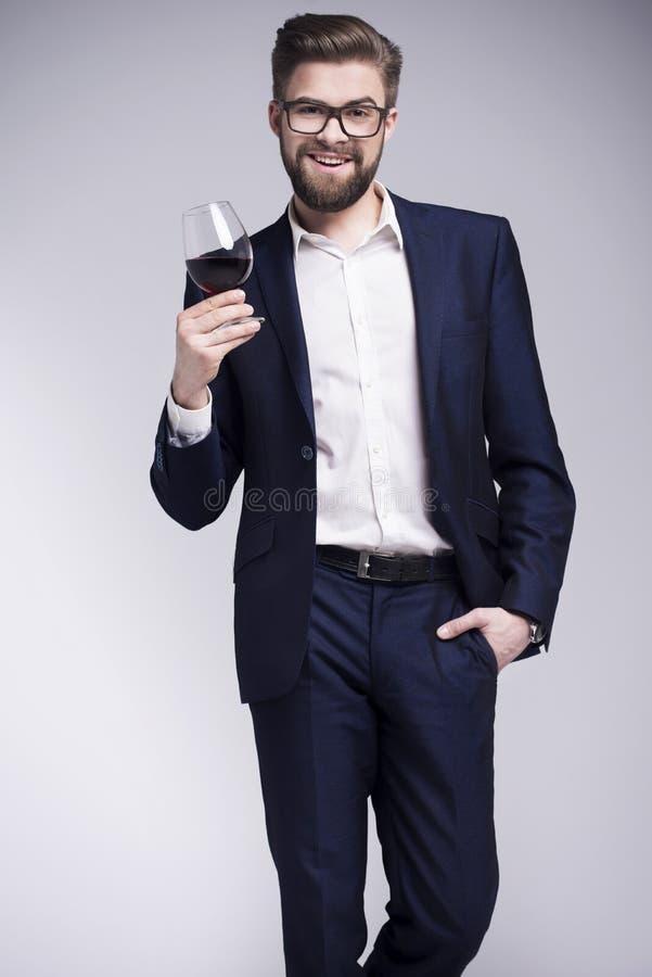Uomo bello con una barba che tiene un bicchiere di vino in sua mano fotografia stock libera da diritti