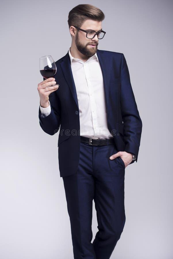 Uomo bello con una barba che tiene un bicchiere di vino in sua mano immagine stock