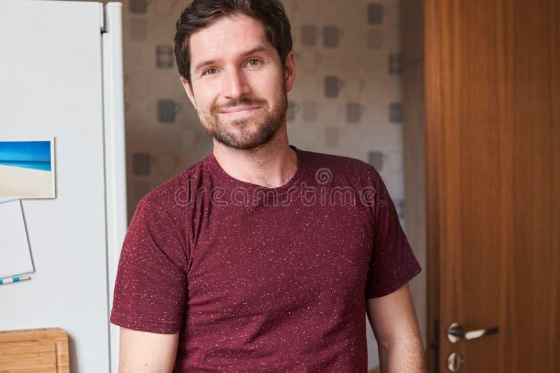Uomo bello contento che sta nella sua cucina a casa fotografie stock libere da diritti