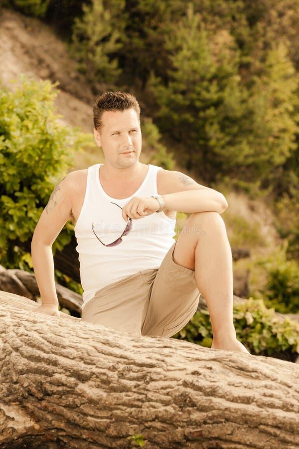 Uomo bello del ritratto di modo che si siede sull'albero fotografia stock