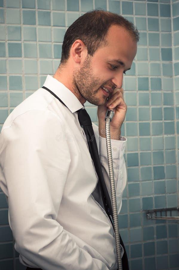 Uomo bello di affari che parla nel bagno con la doccia a disposizione immagini stock