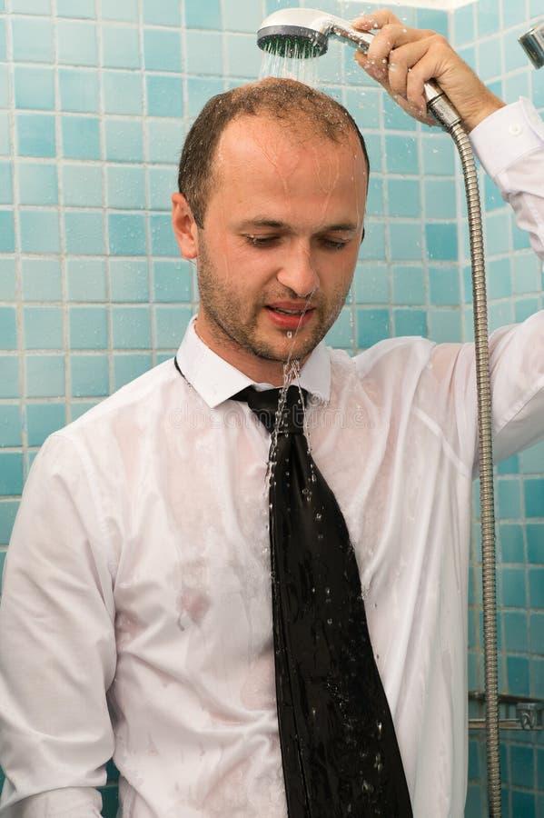 Uomo bello di affari che sta sotto la doccia in camicia immagini stock libere da diritti