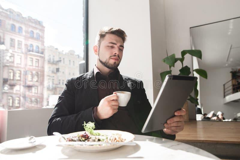 Uomo bello di affari facendo uso di una compressa e di un caffè bevente ad un caffè fotografia stock