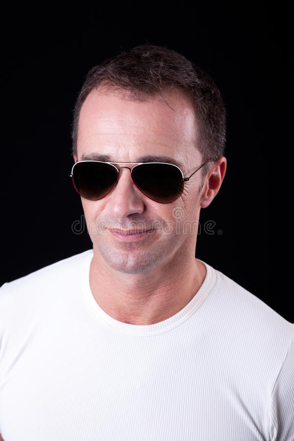 Uomo bello di centrale-età che sorride con gli occhiali da sole immagini stock