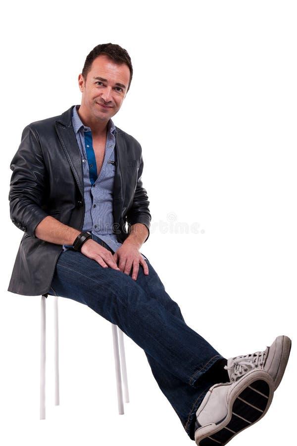 Uomo bello di centrale-età, sedentesi su un banco fotografia stock
