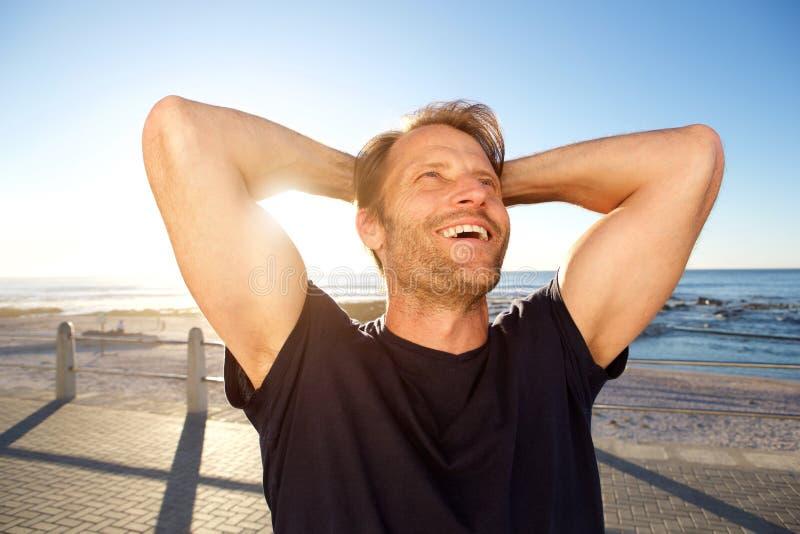Uomo bello di forma fisica che ride con le mani dietro la testa fotografie stock libere da diritti