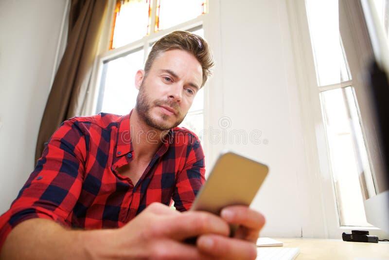 Uomo bello di medio evo che manda un sms sullo Smart Phone immagine stock libera da diritti