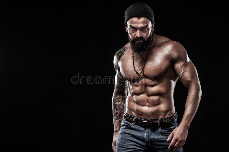 Uomo bello di misura che posa uso in jeans con il tatuaggio Concetto di modo e di sport isolato su fondo nero immagine stock libera da diritti