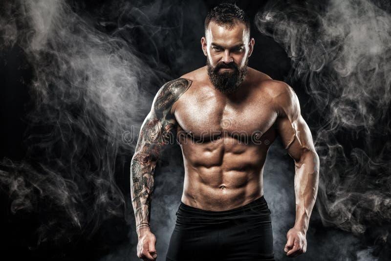 Uomo bello di misura che posa uso in jeans con il tatuaggio Concetto di modo e di sport isolato su fondo nero fotografia stock libera da diritti
