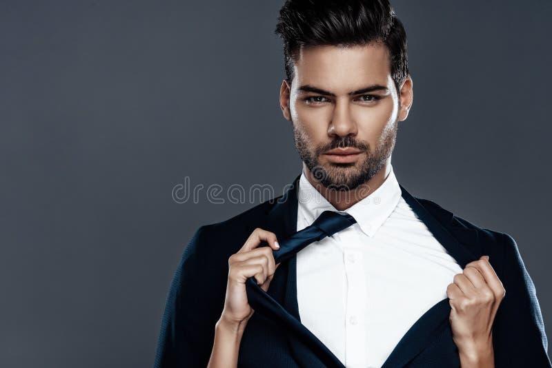 Uomo bello e riuscito del primo piano in un vestito costoso È in una camicia bianca con un legame immagini stock