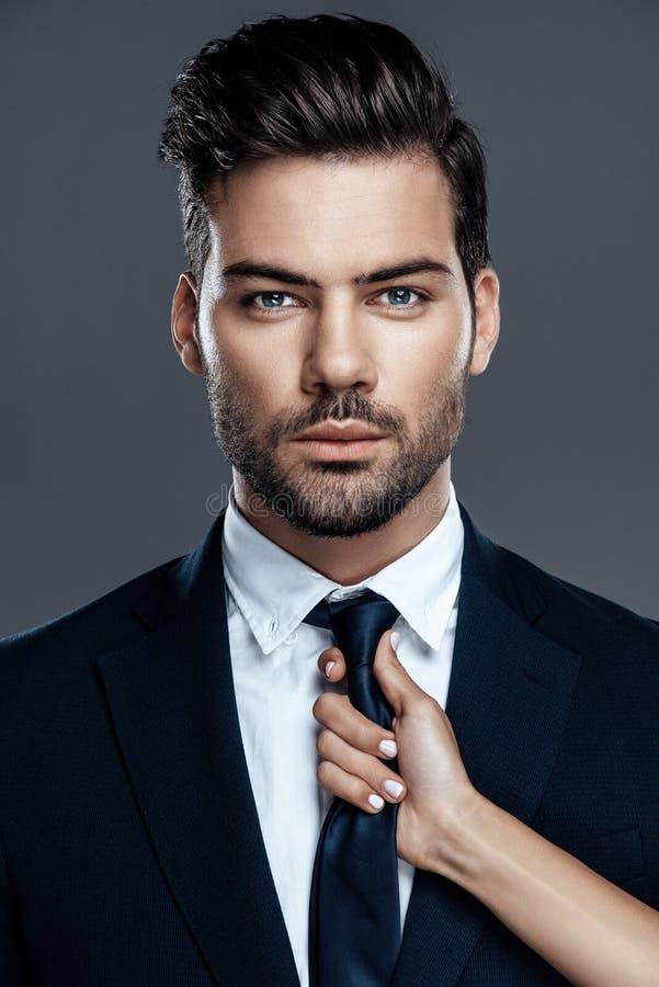 Uomo bello e riuscito del primo piano in un vestito costoso È in una camicia bianca con un legame fotografia stock libera da diritti