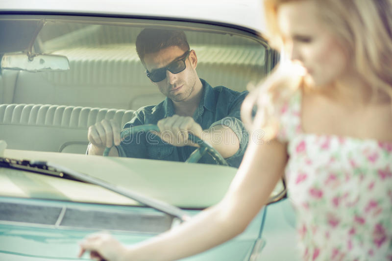 Uomo bello ed alla moda che dà a giovane donna un ascensore fotografia stock