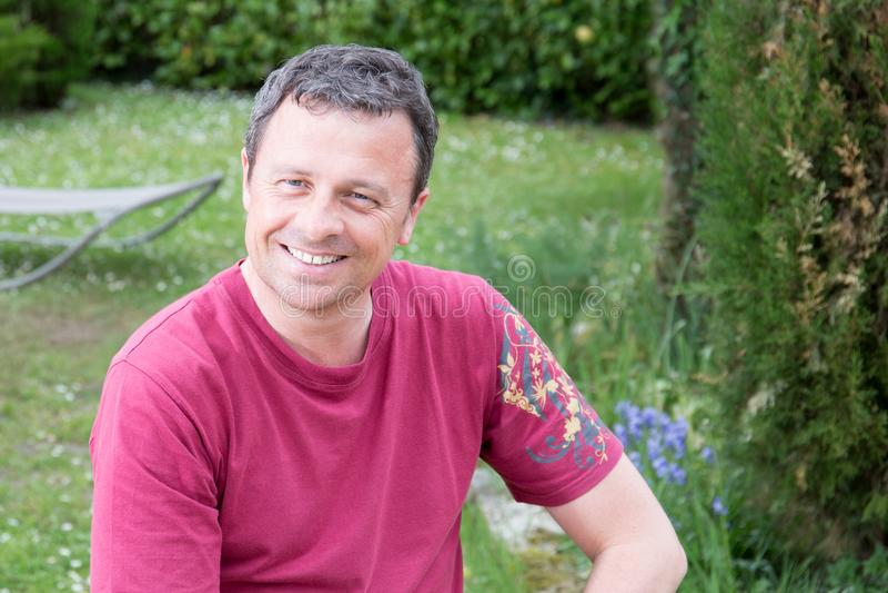 Uomo bello felice all'aperto in giardino domestico fotografia stock