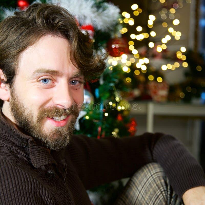 Uomo bello felice con gli occhi azzurri e sorridere lungo di notte di Natale dei capelli e della barba a casa immagine stock