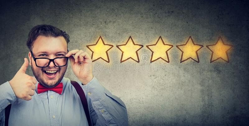 Uomo bello heerful del ¡ di Ð che sorride mostrando pollice su come il gesto che sceglie una valutazione di cinque stelle fotografie stock