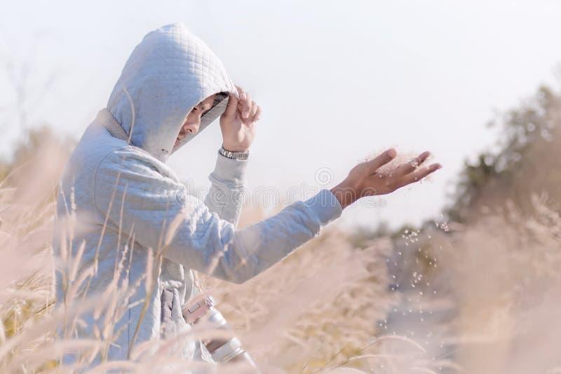 uomo bello misterioso in maglia con cappuccio bianca che sta nell'erba fi fotografie stock libere da diritti