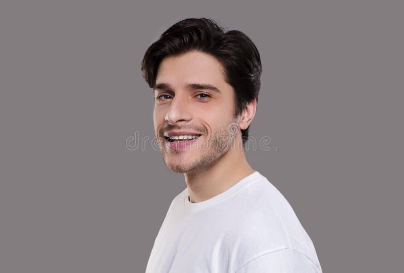 Uomo bello positivo che sorride sul fondo grigio immagine stock libera da diritti