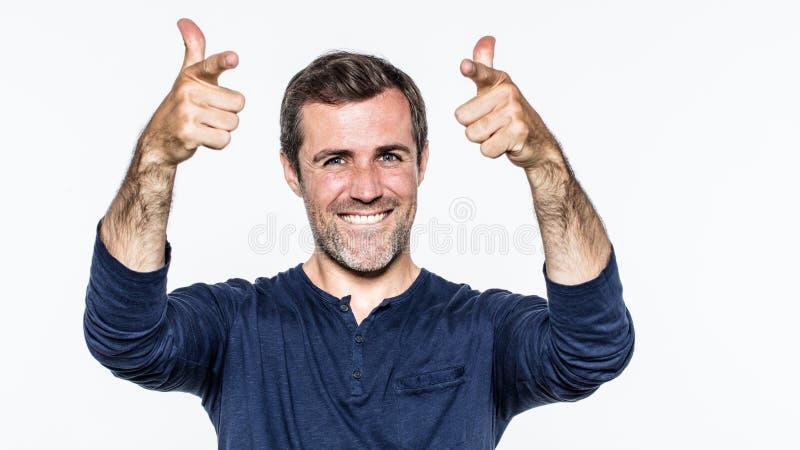 Uomo bello rilassato con gli occhi azzurri che sorride alzando i pollici su fotografia stock