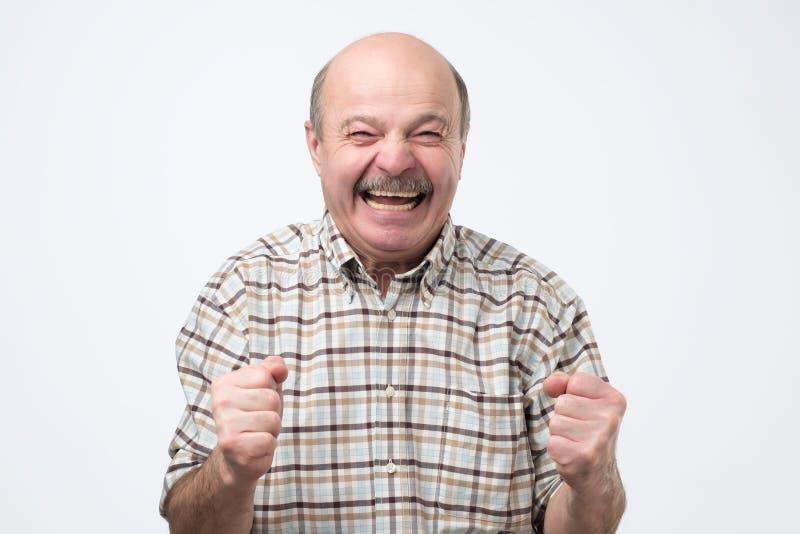 Uomo bello senior che ride e che esamina macchina fotografica con un grande sorriso fotografie stock