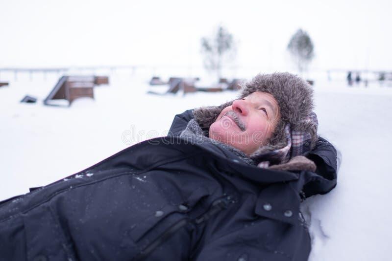 Uomo bello senior in vestiti caldi e cappello che si trovano sulla neve e sul sogno fotografia stock