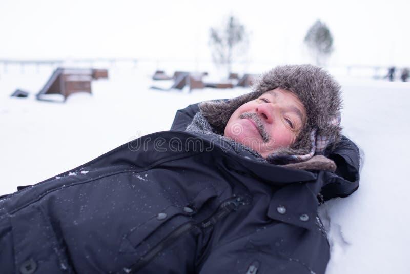 Uomo bello senior in vestiti caldi e cappello che si trovano sulla neve e sul sogno immagini stock