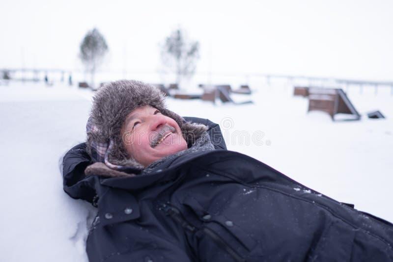 Uomo bello senior in vestiti caldi e cappello che si trovano sulla neve e sul sogno immagine stock libera da diritti