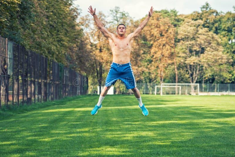 Uomo bello senza camicia che risolve nel parco, addestramento adatto dell'incrocio Uomo atletico che salta e che fa gli esercizi  fotografia stock