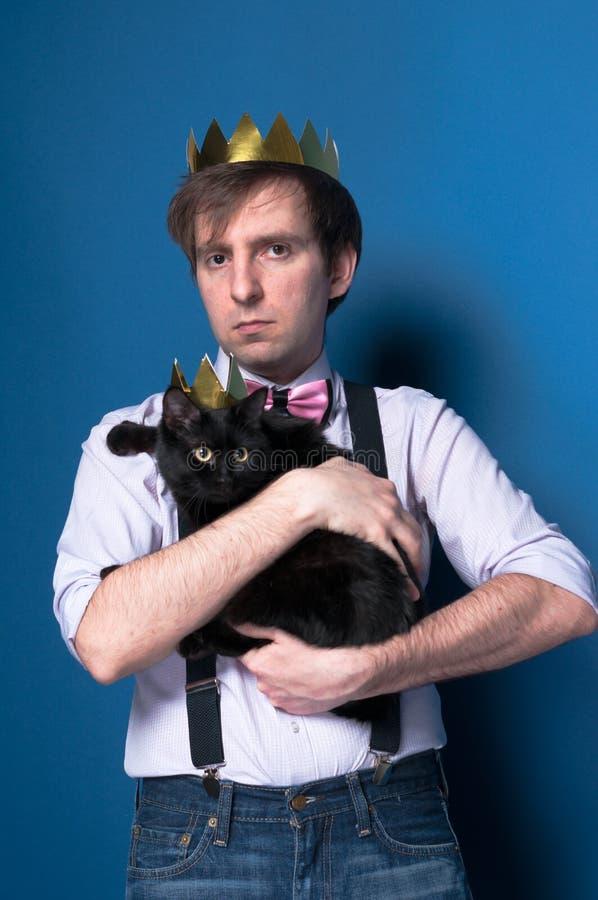 Uomo bello serio in camicia, bretella e corona dorata casalinga tenenti gatto nero in corona brillante fotografia stock libera da diritti
