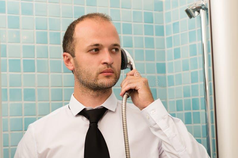 Uomo bello serio di affari che sta nel bagno con la doccia a disposizione fotografia stock