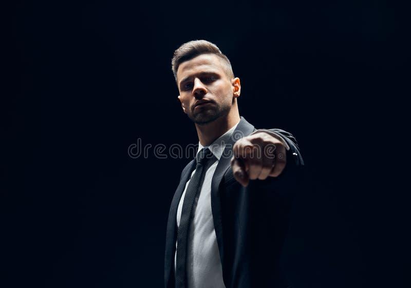 Uomo bello serio in vestito nero che indica il suo dito voi e macchina fotografica isolata su fondo scuro immagini stock