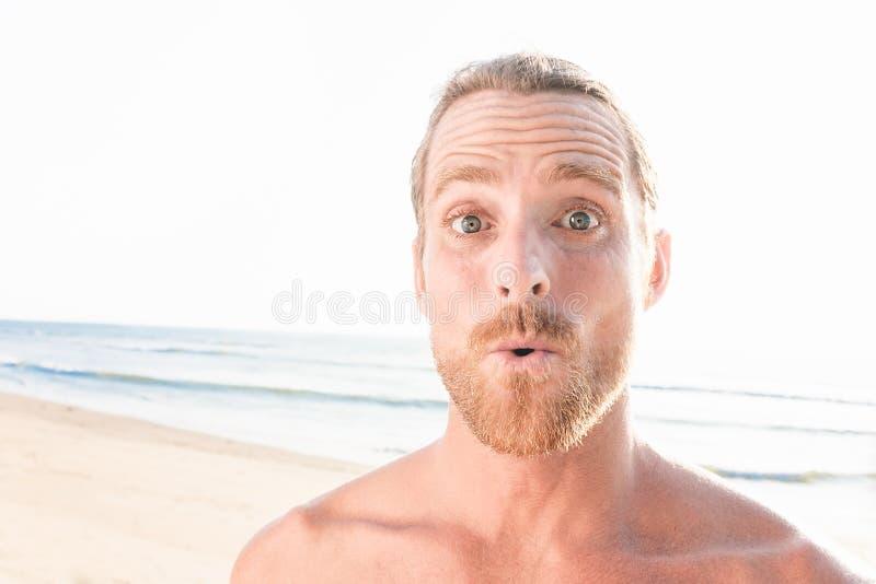 Uomo bello sorpreso alla spiaggia immagini stock