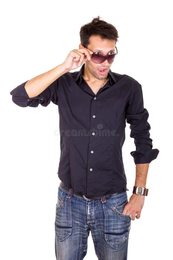 Uomo bello sorpreso che guarda sotto gli occhiali da sole che fanno conta dell'occhio immagini stock libere da diritti