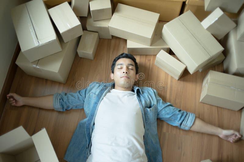 Uomo bello stanco di menzogne d'imballaggio sul pavimento con le scatole e fotografie stock