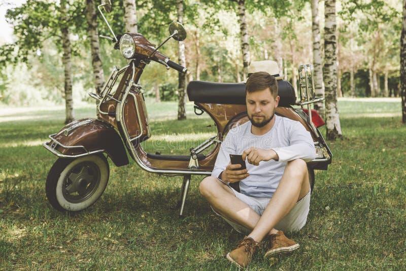 uomo bello su un motorino con un telefono fotografia stock