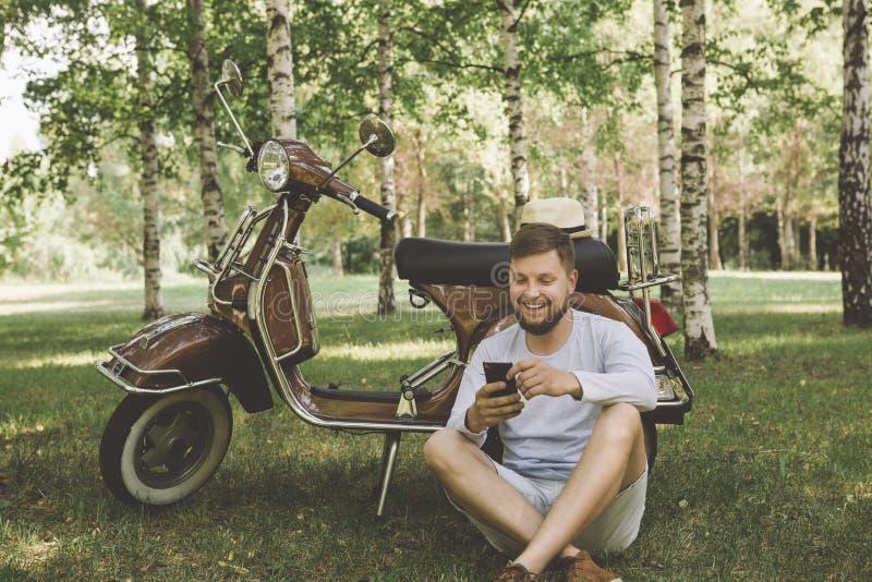 uomo bello su un motorino con un telefono fotografie stock