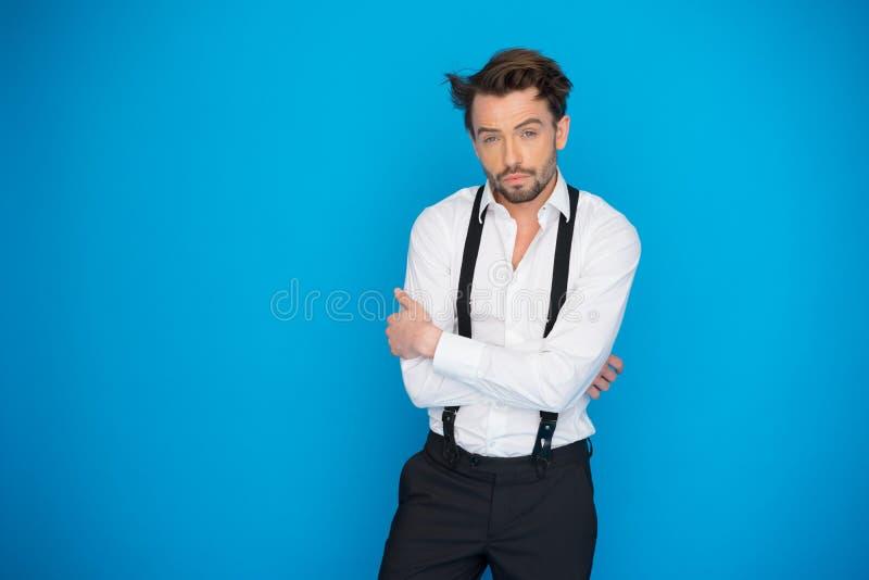 Uomo bello sulla camicia e sui ganci bianchi d'uso del blu fotografie stock libere da diritti