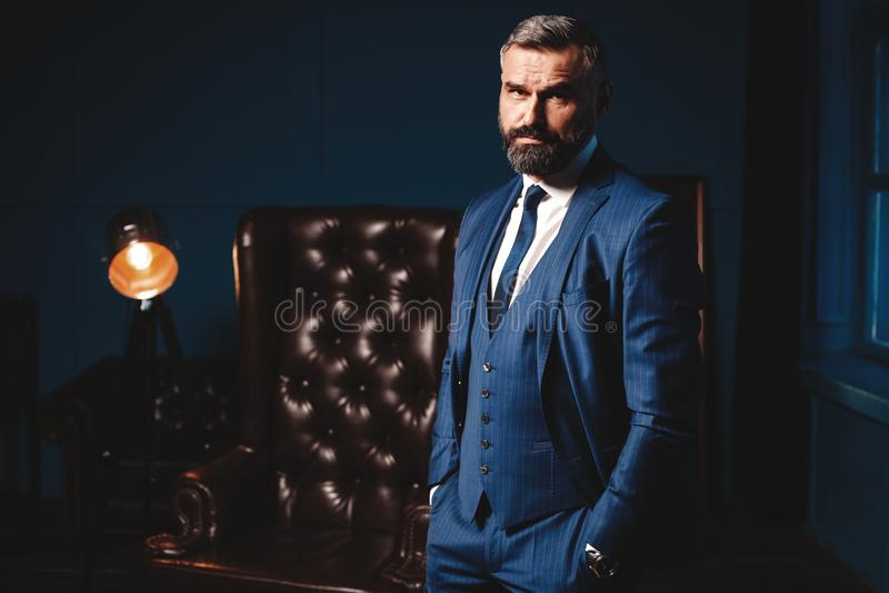 Uomo bello in vestito elegante nell'interno di lusso Ritratto del primo piano dell'uomo sicuro alla moda in appartamento lussuoso fotografia stock libera da diritti