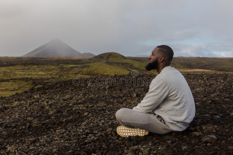 Uomo in bianco in cima seduto sul suolo marrone fotografie stock