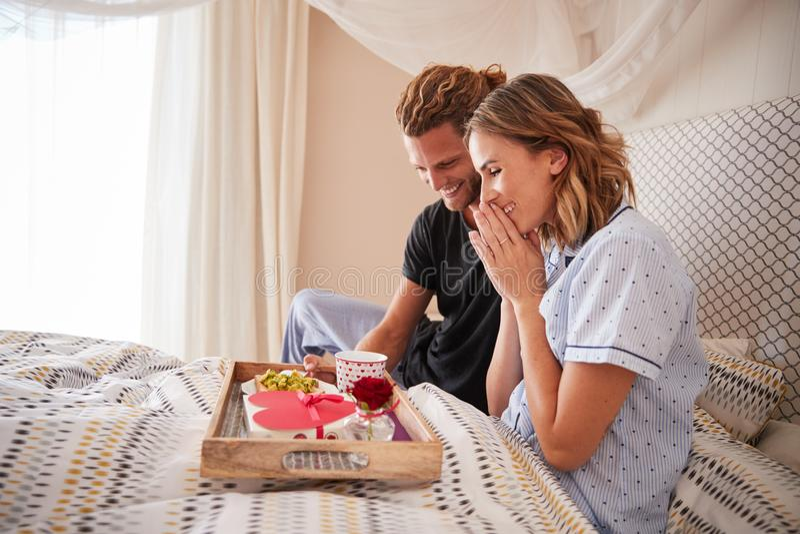 Uomo bianco millenario sorprendente il suo partner femminile con la prima colazione ed i regali a letto, fine su fotografia stock