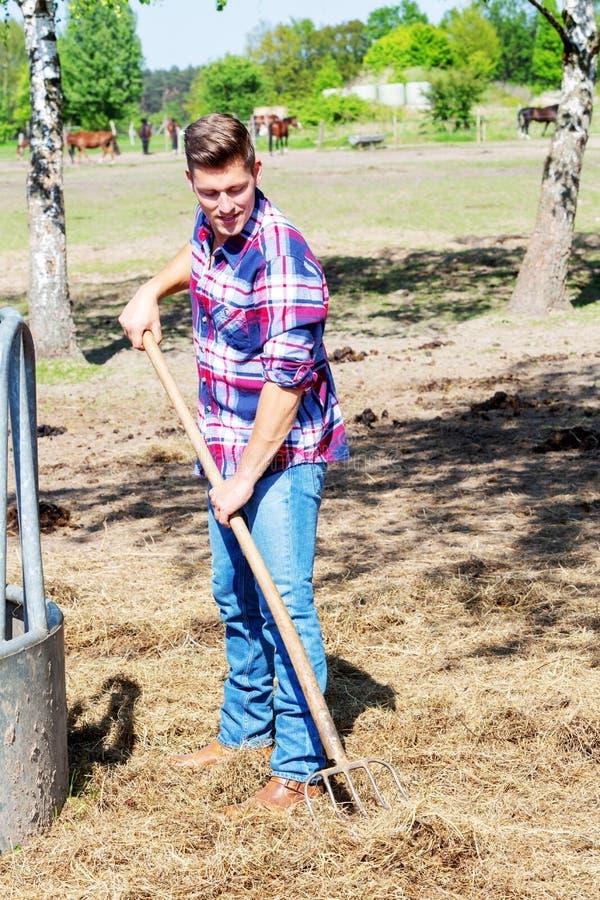 Uomo biondo alla forca holdiing del terreno coltivabile fotografie stock libere da diritti